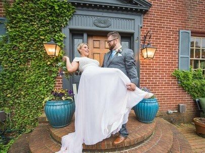 Smiling bride in white dress being dipped by her groom in a grey suit in front of a brick home