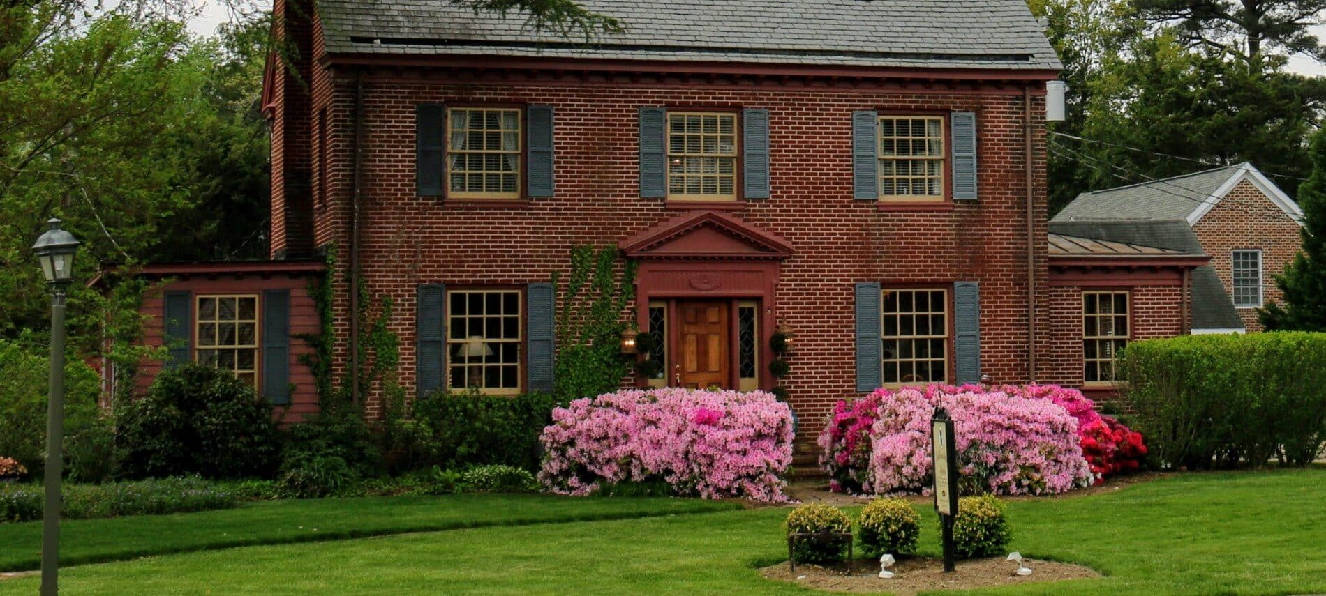 Front facade of an elegant red brick home with several windows and tall pink flowering shrubs by the front path