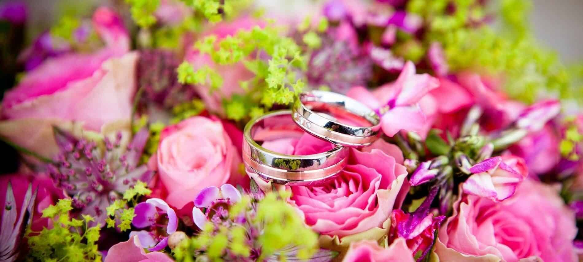 Gorgeous array of pink and purple flowers with an up close view of two silver wedding bands sitting on top