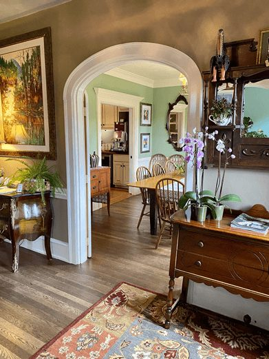 Beautiful arched doorway in a home with a view of an entryway and dining room with large table and doorway into a kitchen