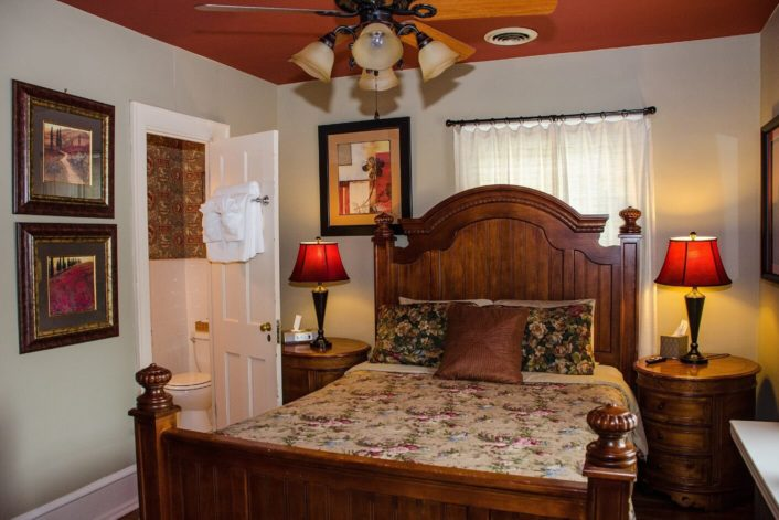 Guest room featuring queen bed with tall brown headboard with window behind, round side tables and doorway into bathroom
