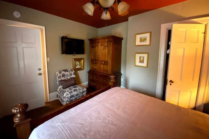 Guest room featuring queen bed in white linens, brown armoire next to sitting chair and TV on the wall