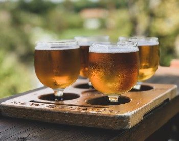 Wooden platter featuring a flight of four short glasses of light colored beer