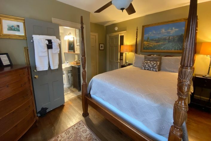 Cozy guest room with four poster bed in white bedding, brown dresser and side tables and doorway into small bathroom