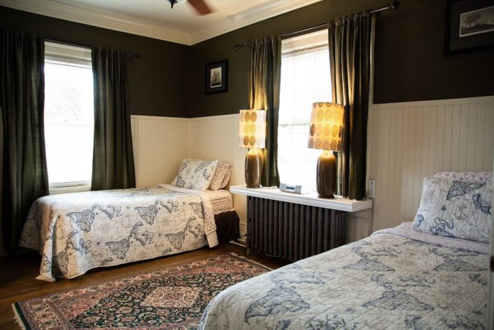 Two twin beds in guest room with black and white walls, large window and oriental rug on the floor