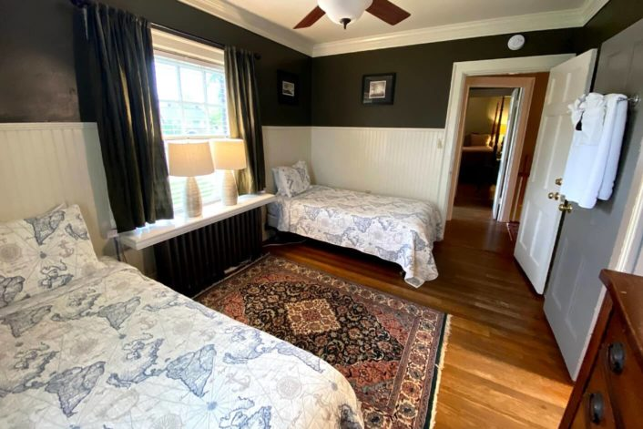 Guest room with two twin beds in front of large window with oriental rug on the floor and doorway into second bedroom