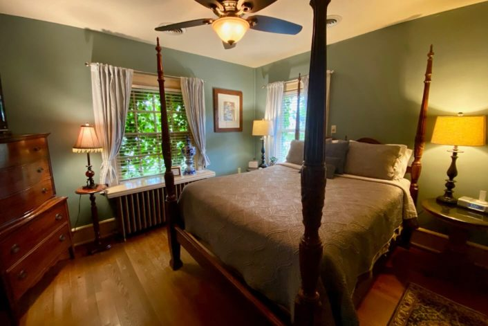 Four poster bed in luxurious guest room with green walls, brown accent furniture and large bright windows