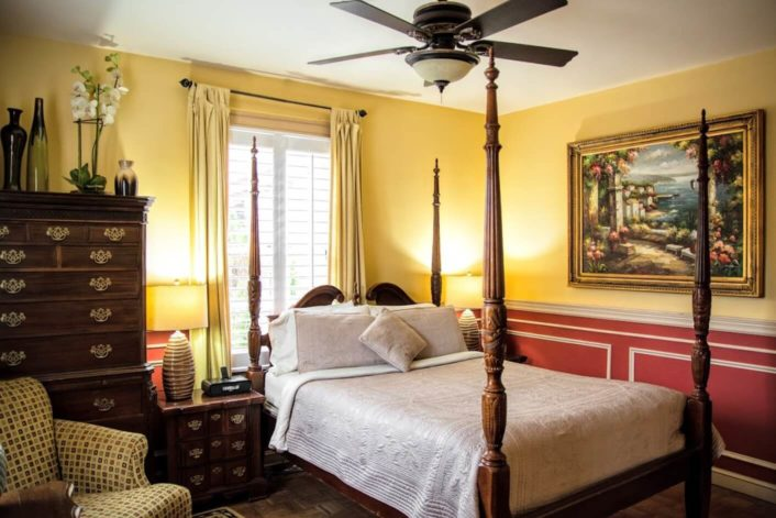 Four poster bed in guest room with red and yellow walls, dark brown dresser and side table, and upholstered chair