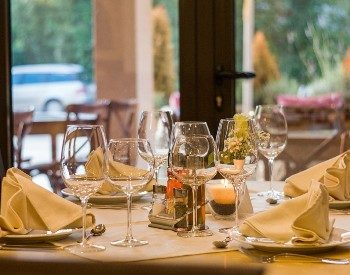 Table in a fine dining restaurant with white linens, white dishes and clear wine glasses