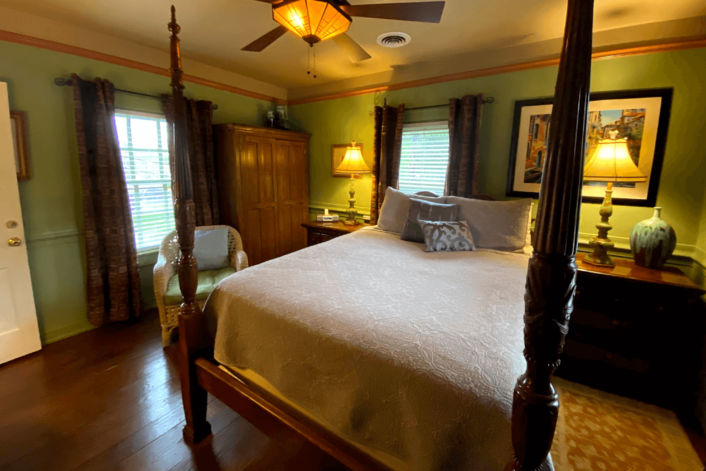 Spacious guest room with dark brown four poster bed, side tables with lamps, armoire and paintings on the wall