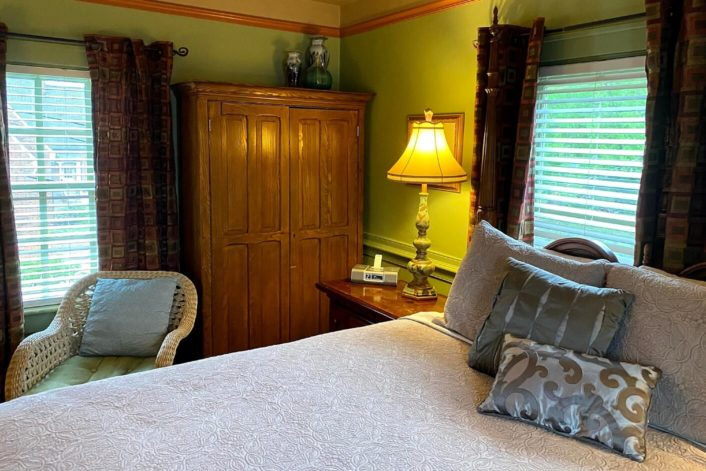 Cozy guestroom with grey bedding and pillows, tall brown armoire, chair, two windows and side table with lamp