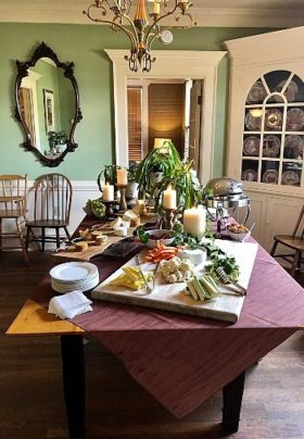 Dining table withe chairs pushed aside featuring a buffet of a variety of foods and tall white candles