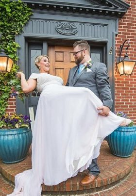 Groom in grey suit dipping a smiling bride in white at the doorway of a red brick home