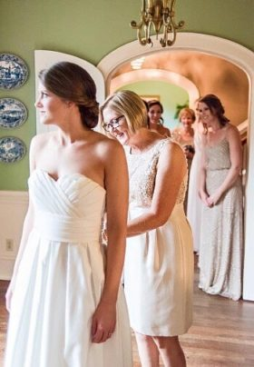 Mother of the bride attending to a bride's dress while bridesmaids look on in the background