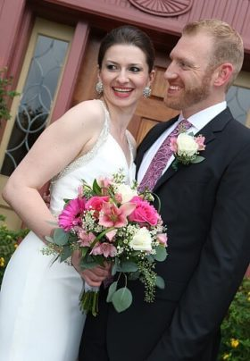 Smiling bride holding a pink and white bouquet next to her groom in black in front of a door outside