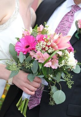 Groom in black suit next to a bride in white holding a flower bouquet of pink and white flowers