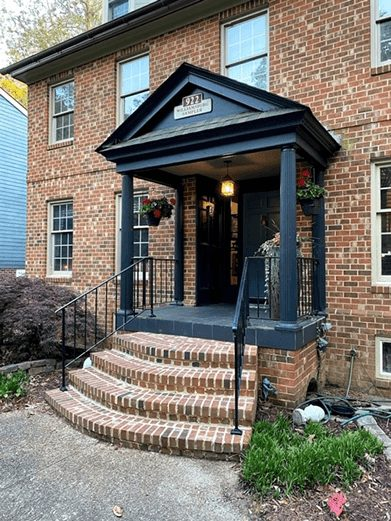 Front porch of a brick home with black peaked overhang, curved steps and hanging baskets by door